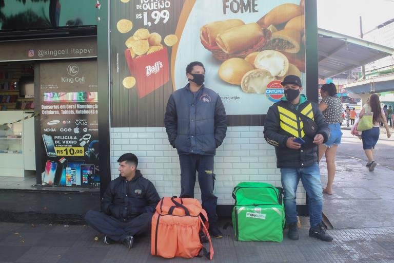 motociclistas aguardam entrega em frente a restaurante, alguns estão sentados no chão e outros de pé com mochilas ao lado