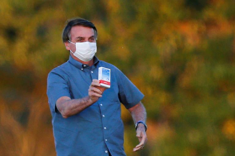 Bolsonaro de máscara segurando com uma das mãos uma caixa de medicamento
