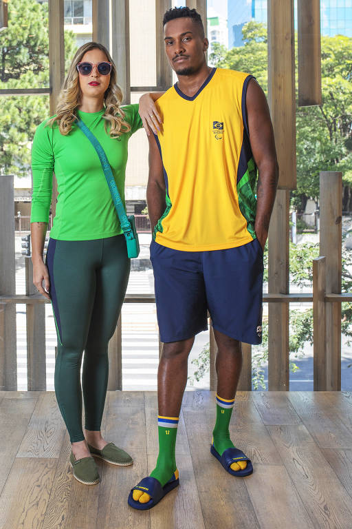 Mulher apoia o braço no ombro de um homem ao seu lado; eles estão em pé, vestidos com as novas roupas esportivas do esporte paraolímpico, nas cores verde, amarela e azul; ela, que possui deficiência visual, está de óculos com lentes escuras