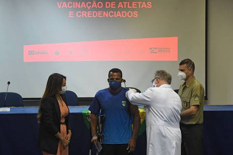 Brazilian rowing paralympic athlete Michel Pessanha (C) is inoculated with a COVID-19 vaccine by Brazil's Health Minister Marcelo Queiroga as part of a project organized by the Brazilian federal government to vaccinate Brazilian citizens accredited to the Tokyo Olympic Games amid the COVID-19 pandemic in Rio de Janeiro state, Brazil, on May 14, 2021. (Photo by MAURO PIMENTEL / AFP)