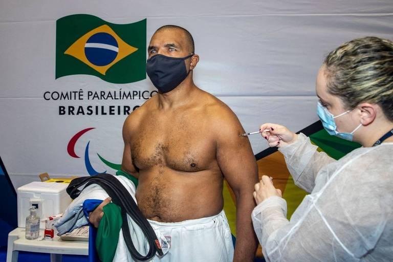 Segurando o kimono numa mão e sem camisa, homem recebe aplicação de vacina no braço