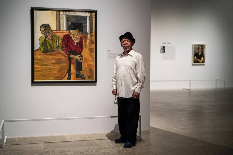 Homem negro idoso ao lado de pintura