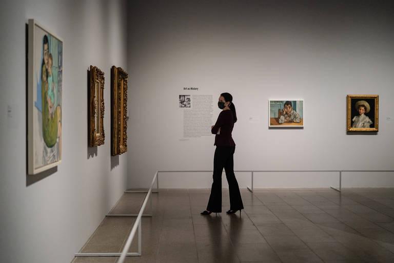 Mulher olha quadros em museu