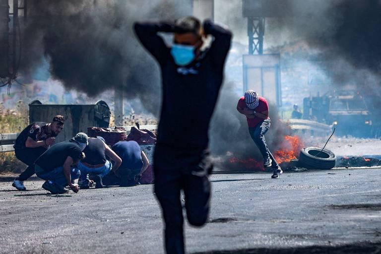 Manifestante palestino corre durante confronto com forças israelenses na cidade de Nablus, na Cisjordânia