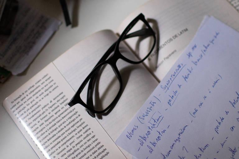 Mesa com livro, anotações e óculos do cientista Marcelo Menin, morto por Covid-19