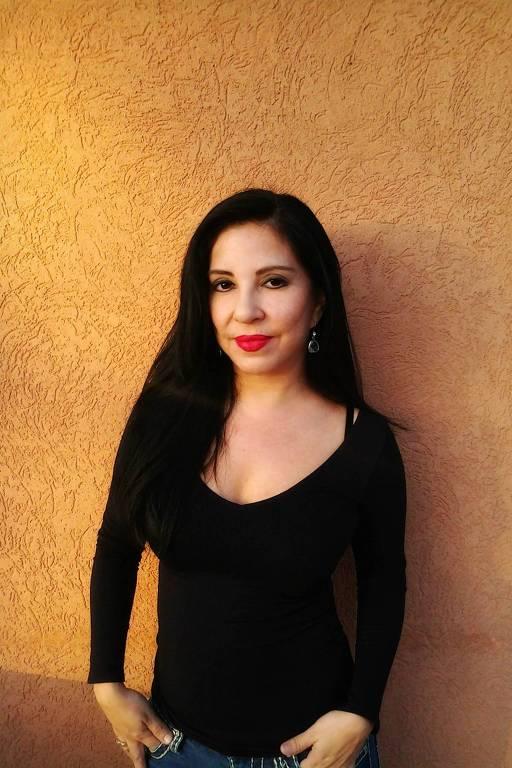 mulher branca de cabelos pretos longos e batom vermelho posa diante de parede texturizada alaranjada