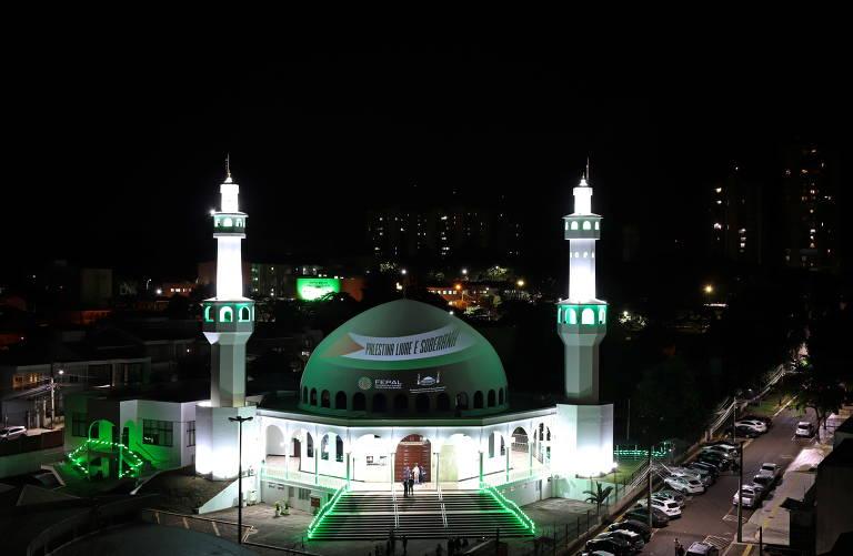 Cena noturna, a mesquista é vista ao longe, iluminada, com a inscrição na cúpula