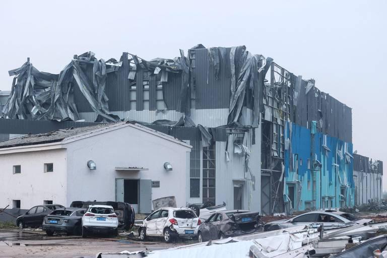 Imagem mostra carros destruidos e residencias destelhadas, com céu nublado ao fundo