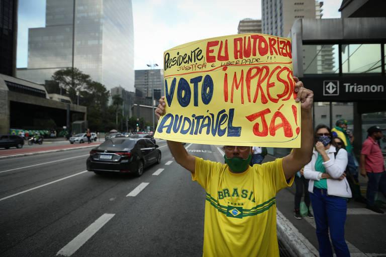 """homem veste camiseta amarela do brasil e segura cartaz em que se lê """"bolsonaro, eu autorizo voto impresso e auditável já"""""""
