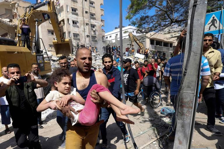 Imagem mostra homem carregando menina, suja de pó, em meio aos escombros do local