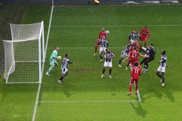 Momento em que o goleiro Alisson cabeceia para marcar o gol da vitória do Liverpool sobre o West Browmich, em partida válida pelo Campeonato Inglês