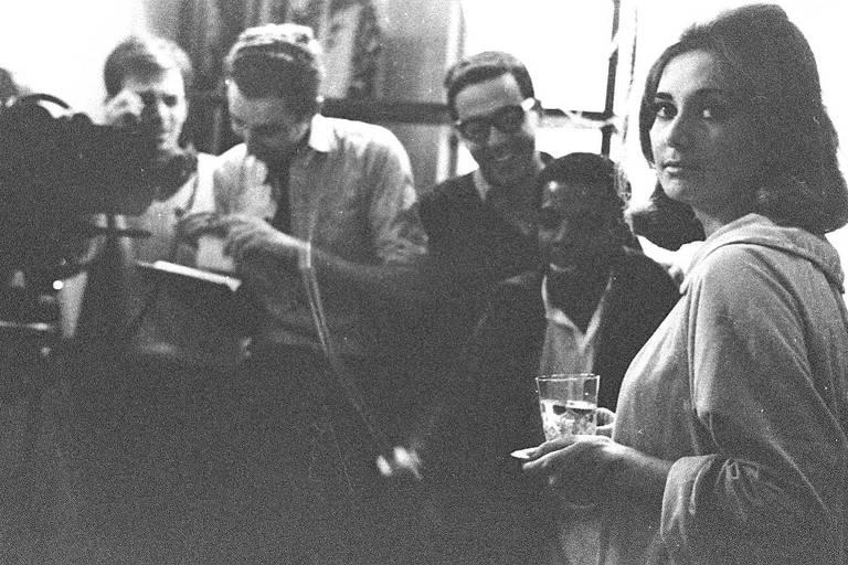 mulher no canto da imagem olhando para a camera segura copo d'água, ao fundo, homens com câmera de cinema