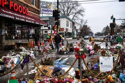 A man walks in the makeshift memorial of George Floyd before the third day of jury selection begins in the trial of former Minneapolis Police officer Derek Chauvin who is accused of killing Floyd, in Minneapolis, Minnesota on March 10, 2021. - The first jurors were selected on March 9, 2021 in the high-profile trial of the white police officer accused of killing George Floyd, an African-American man whose death laid bare racial wounds in the United States and sparked