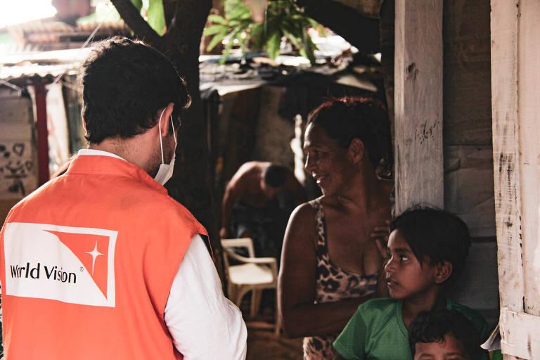 homem de jaqueta laranja conversa com mulher e sua filha em frente a uma casa em comunidade