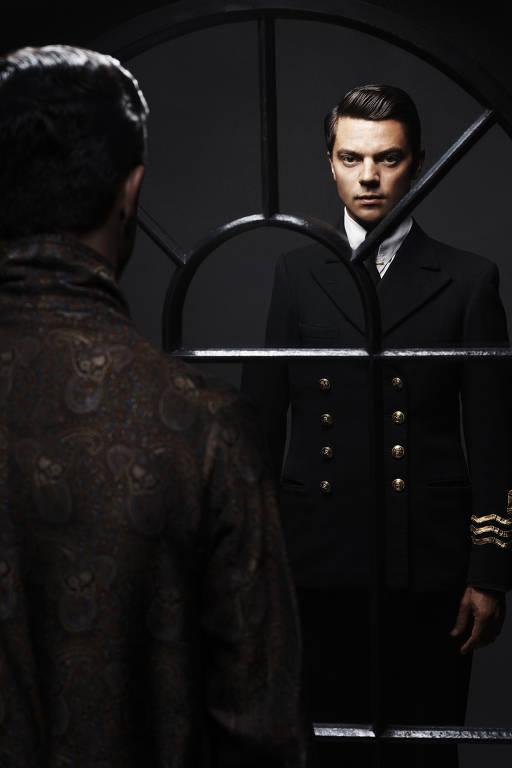 homem branco de terno se encara no espelho