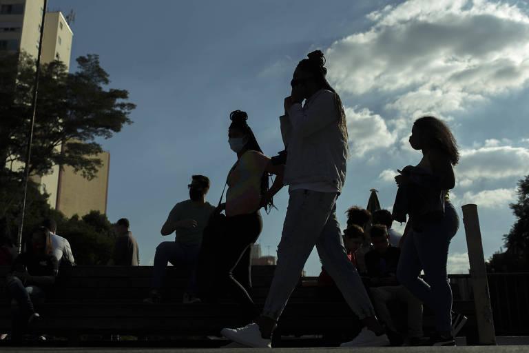 Foto mostra pessoas sentadas juntas e outras passando na rua; não se veem seus rostos, porque a luz vem de trás, do céu azul com nuvens