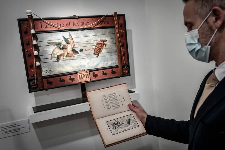 Homem com máscara facial olha livro em frente à quadro na parede