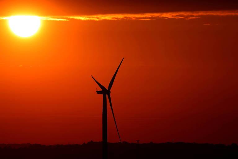 O sol nasce atrás de uma turbina eólica