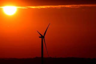 FILE PHOTO: The sun rises behind a wind turbine in Halle, Belgium