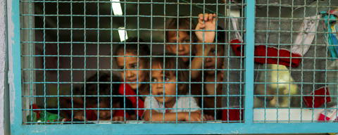 A Palestinian boy, who fled his family's home due to Israeli air and artillery strikes, looks on as other children look through a window fence at a United Nations-run school where they take refuge, in Gaza City May 18, 2021. REUTERS/Suhaib Salem ORG XMIT: FW1
