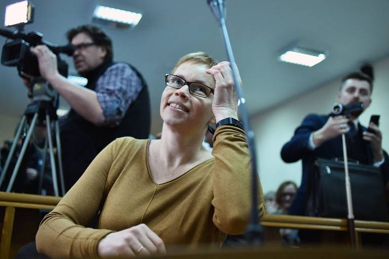 Moça de cabelos loiros bem curtos e óculos de armação redonda sorri com a mão esquerda na testa