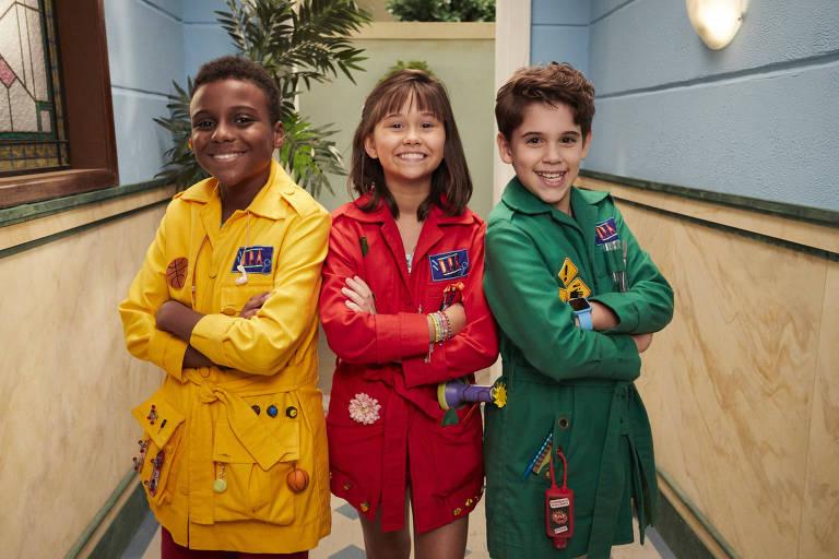 Três crianças com capas coloridas, de braços cruzados, sorriem para a câmera em um corredor azul