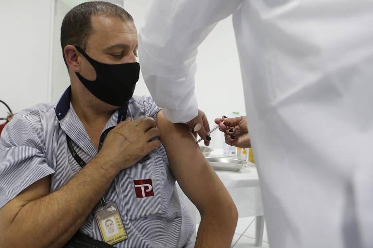 Homem de máscara preta e camisa cinza é vacinado no braço por profissional de jaleco branco