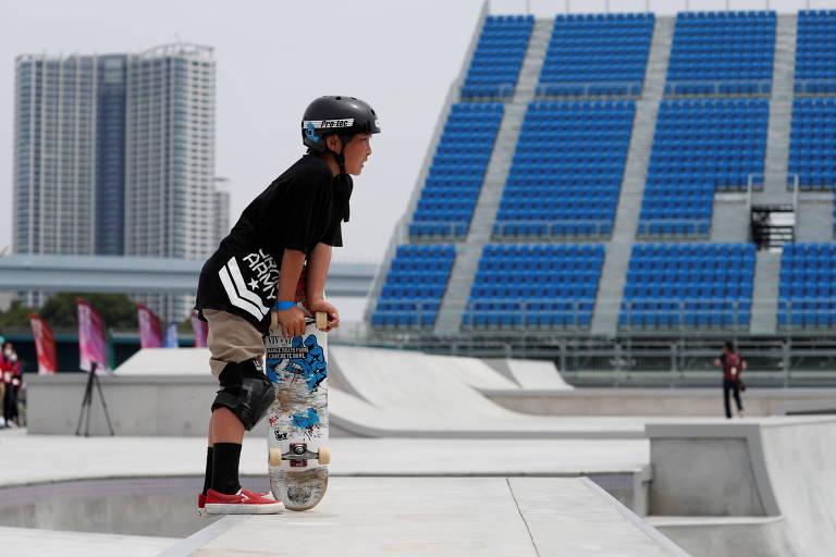 Skatista segura o skate e olha para frente em frente a arquibancada vazia