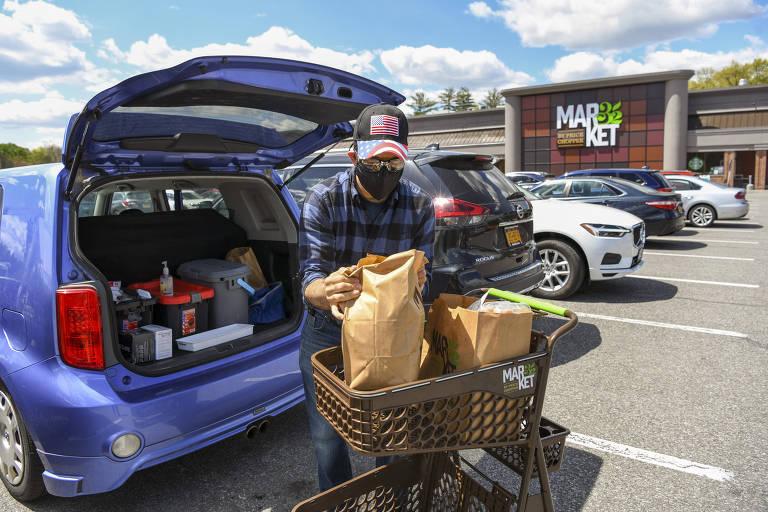 Senhor com máscara guarda compras em seu carro