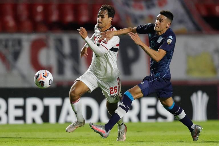O são-paulino Igor Gomes arranca ao ataque com a bola e é seguro pelo ombro direito pelo jogador argentino Mauricio Martínez