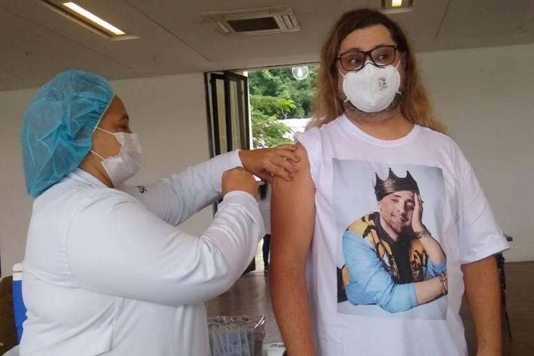 Marcus Majella recebe vacina da Covid com camiseta de Paulo Gustavo
