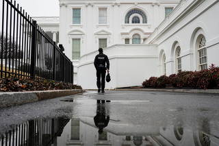 A Secret Service officer walks on the White House grounds in Washington