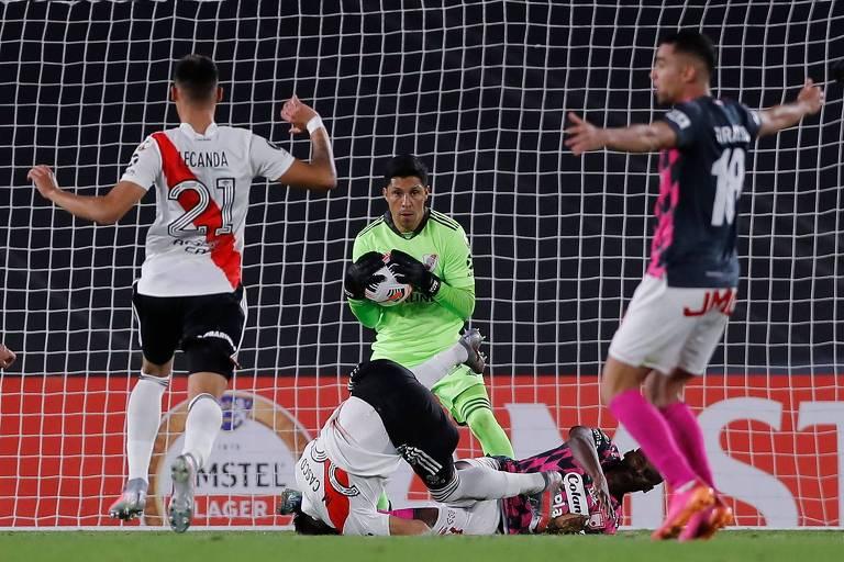 Improvisado como goleiro, o meia Enzo Pérez agarra a bola durante a partida em que o River Plate derrotou o Independiente Santa Fe, em Buenos Aires