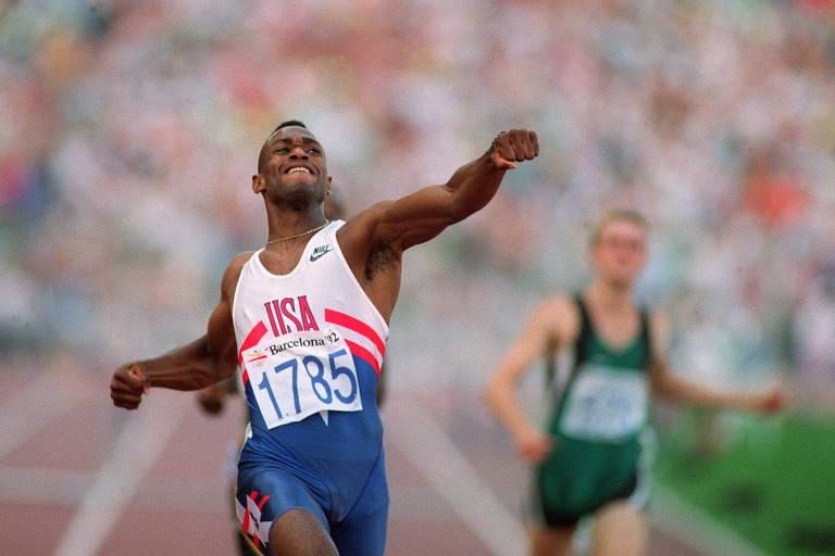 Atleta com roupa de corrida nas cores branca, azul e vermelha sorri com os braços esticados