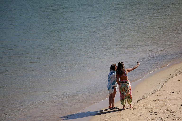 Duas mulheres fazem selfie pisando na divisa entre a areia de o mar em praia de águas calmas