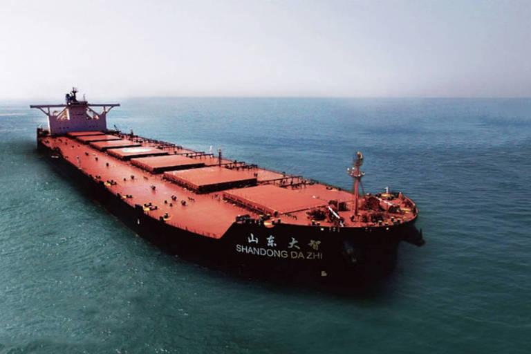 Foto horizontal mostra navio vermelho, no mar verde, contra céu azul