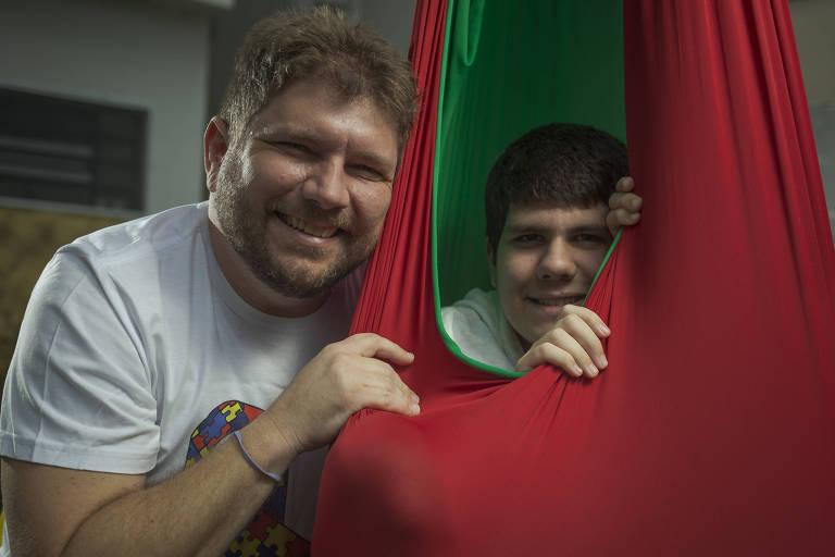Rafael Abreu Mendes, 42, e o filho Francisco, 14, no balanço de laicra da marca Alma Azul, desenvolvida  pelo pai em 2012 para pessoas com TEA (Transtorno do Espectro Autista)
