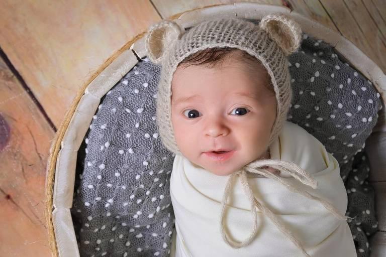 O bebê Enrico usa touca com orelhinhas e está enrolado em uma manta branca