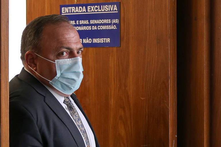 Foto mostra Pazuello de terno, gravata e máscara cirúrgica azul, no batente de uma porta do Senado, que diz ENTRADA EXCLUSIVA