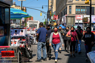 Pedestrians wear face masks while walking in the Bronx on Wednesday, May 19, 2021. (Desiree Rios/The New York Times)
