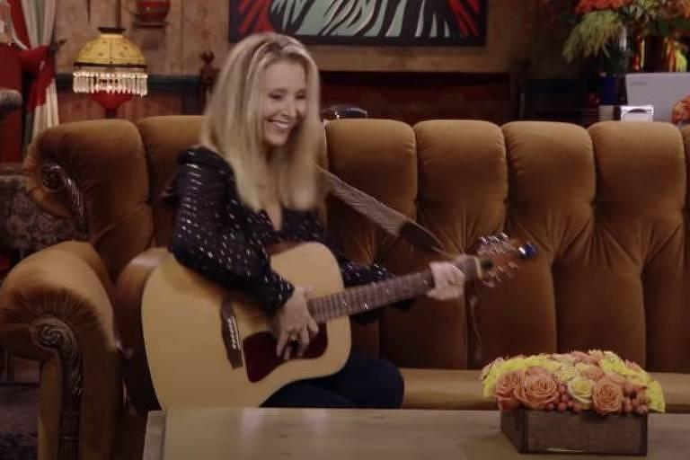 Lisa Kudrow com o famoso violão em que Phoebe Buffay tocava músicas com suas letras hilárias e por vezes constragendoras
