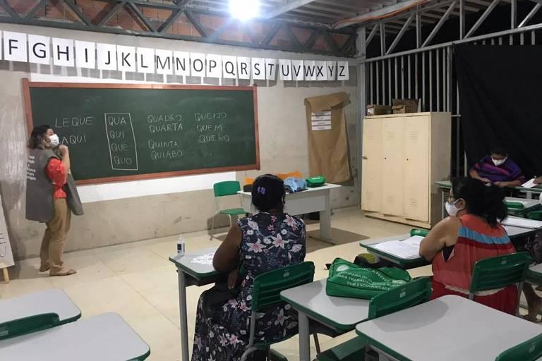 mulheres de costas sentadas em carteiras escolares com professora ao fundo na lousa