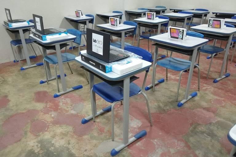 computadores e tablets estão em cima de carteiras escolares dentro de uma sala que fica na penitenciária