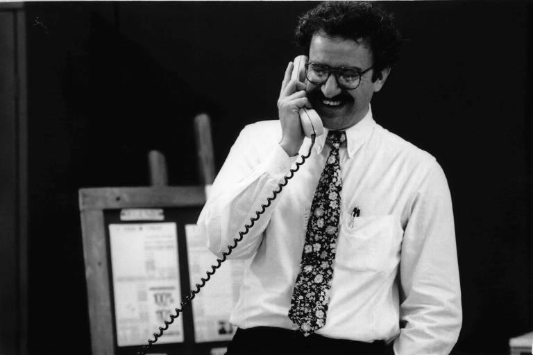 Homem branco de cabelos e bigodes pretos, óculos, camisa branca e gravata estampada, falando ao telefone e rindo.