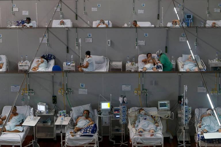 Fileiras de camas com pacientes separadas por paredes finas