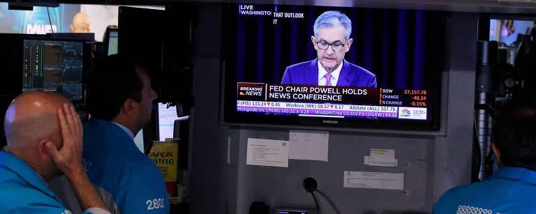 Operadores da Bolsa de Valores de Nova York observam uma tela que mostra a coletiva de imprensa do presidente do Fed, Jerome Powell