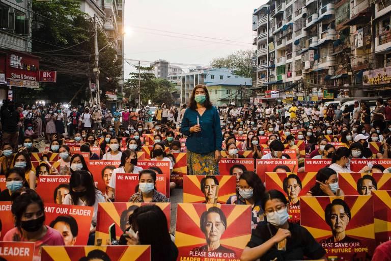 Há uma rua cheia de manifestantes, quase todos sentados, carregando cartazes com as cores vermelho e laranja e o rosto de Suu Kyi. No meio dos manifestantes sentados há uma em pé, com uma camisa azul e um microfone.