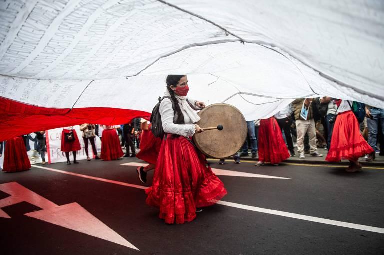 Mulher com trajes típicos sob tecido branco e vermelho