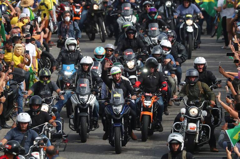 O presidente Jair Bolsonaro (sem partido) acena para apoiadores enquanto passa de moto por via no Rio de Janeiro neste domingo (23)