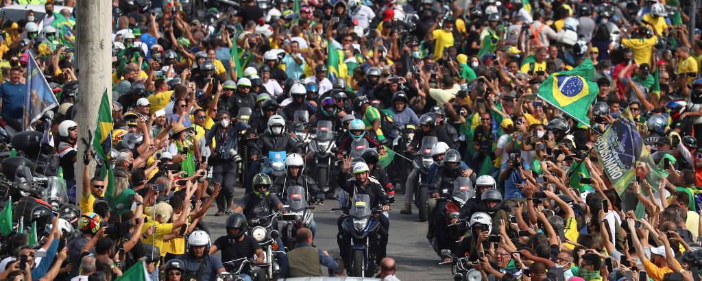 Aglomeração de pessoas saúda motociclistas, com caminhonete branca à frente